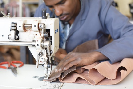 Hand stitching the Ethiopian Leather Purse.