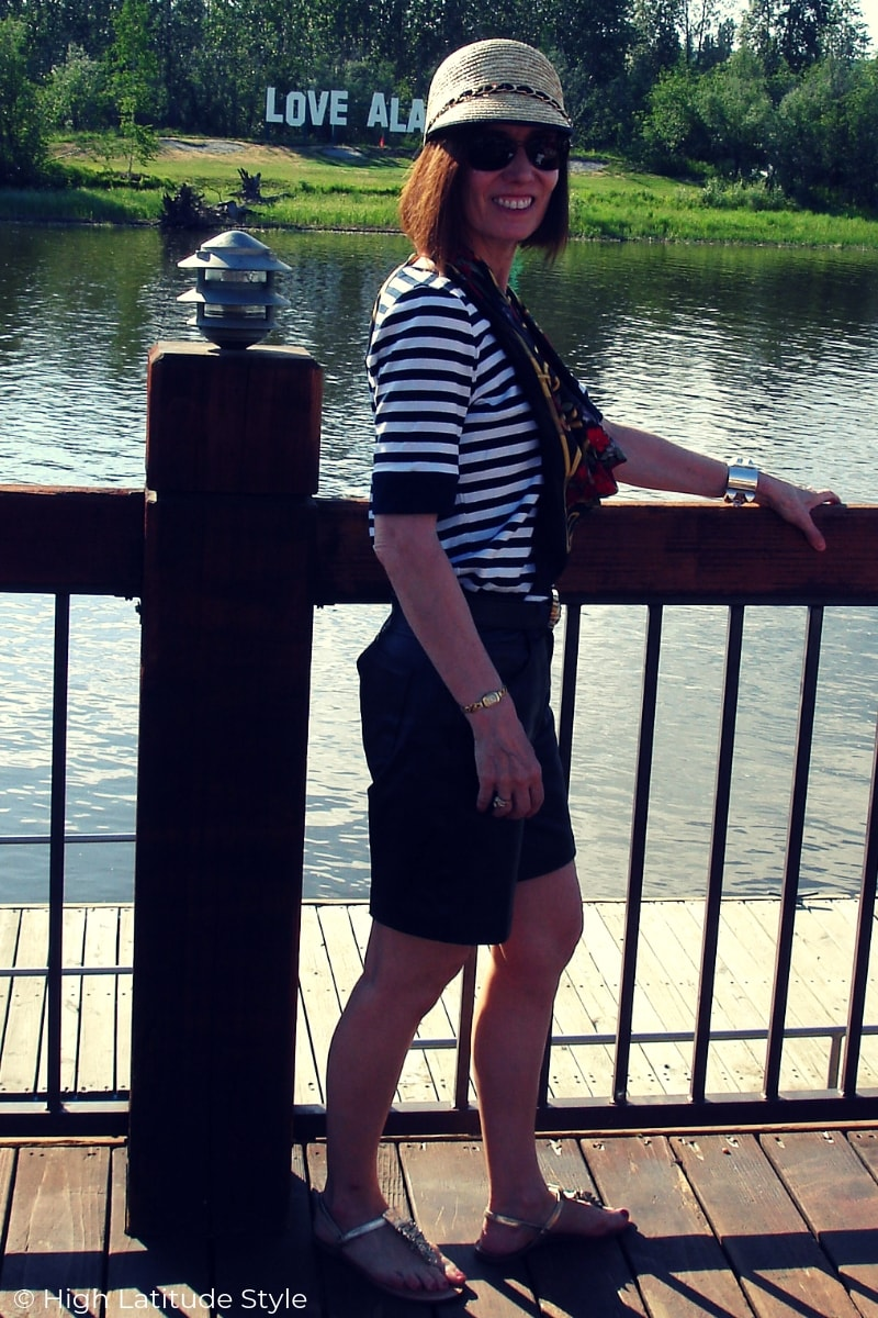 over 50 years old style blogger in biker leather shorts, striped top, floral scarf and straw cap at the river on a deck