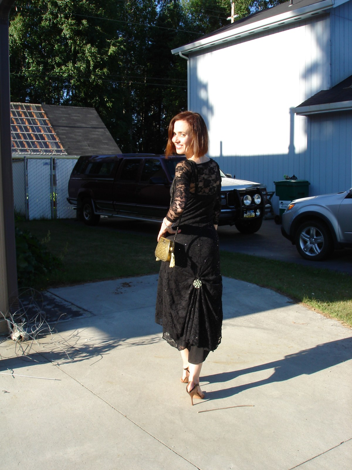 style blogger Nicole in a black lace dress with clasp decoration on tail