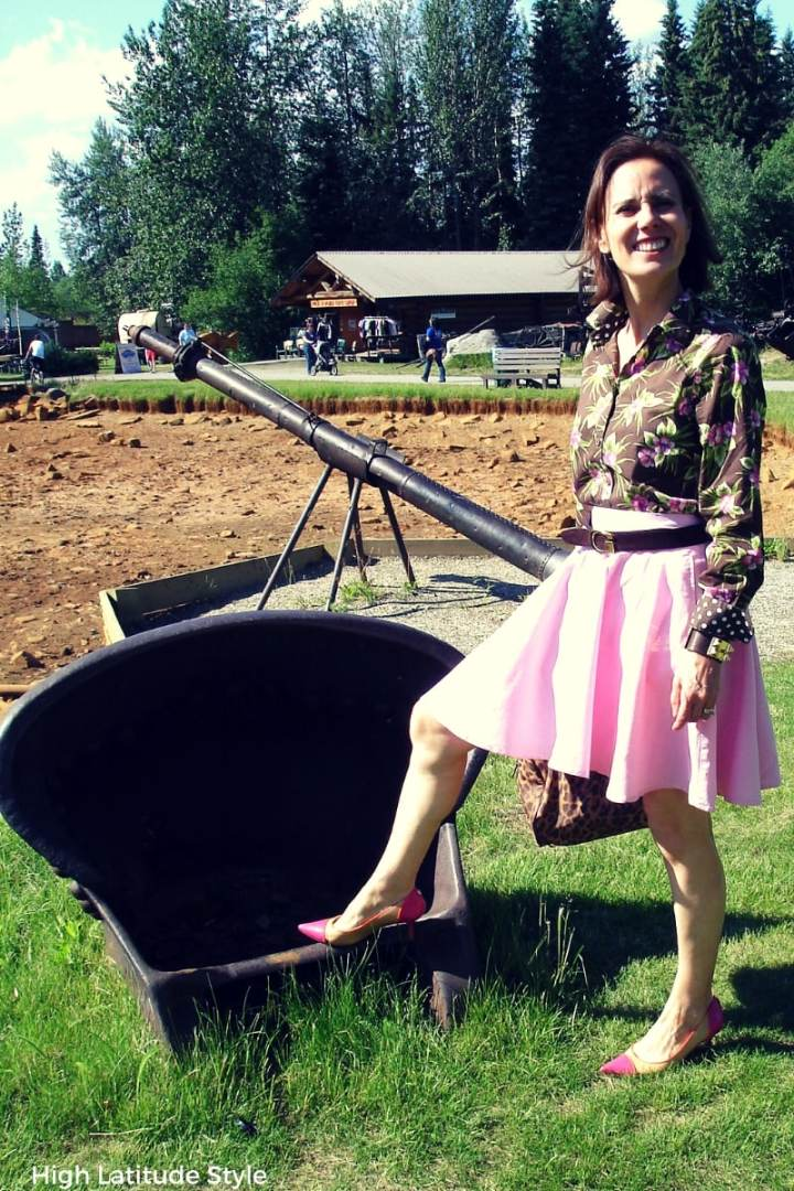 Alaskan fashion blogger in skater skirt and Hawaiian shirt posing in front of mining equipment