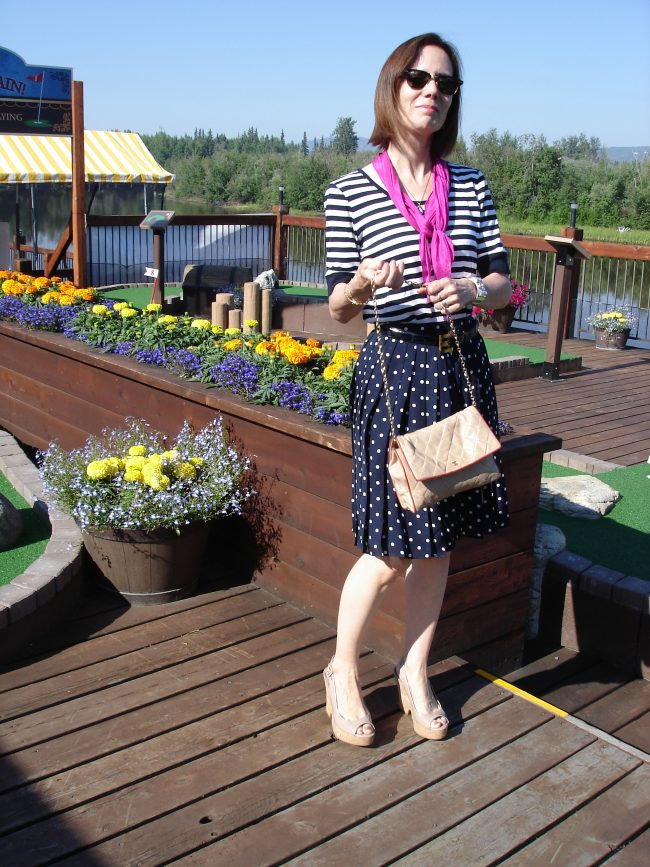 style blogger in blue white geometric prints with polka dot pleated skirt and striped T-shirt with nude plateau sandals