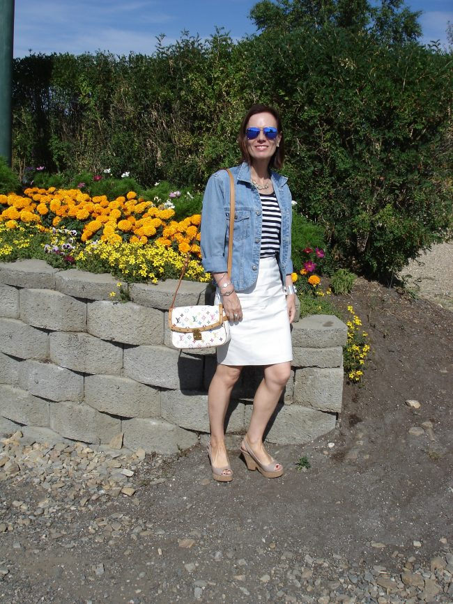 stylist in spring look with striped T-shirt white skirt tailored denim jacket plateau sandals mirrored sunnies