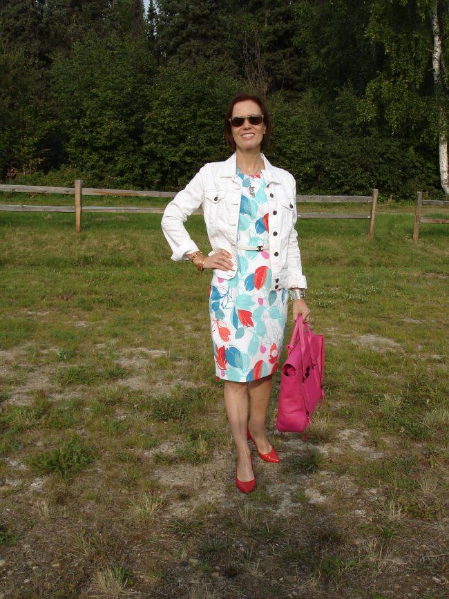 influencer in white print dress with white denim jacket fuchsia bag