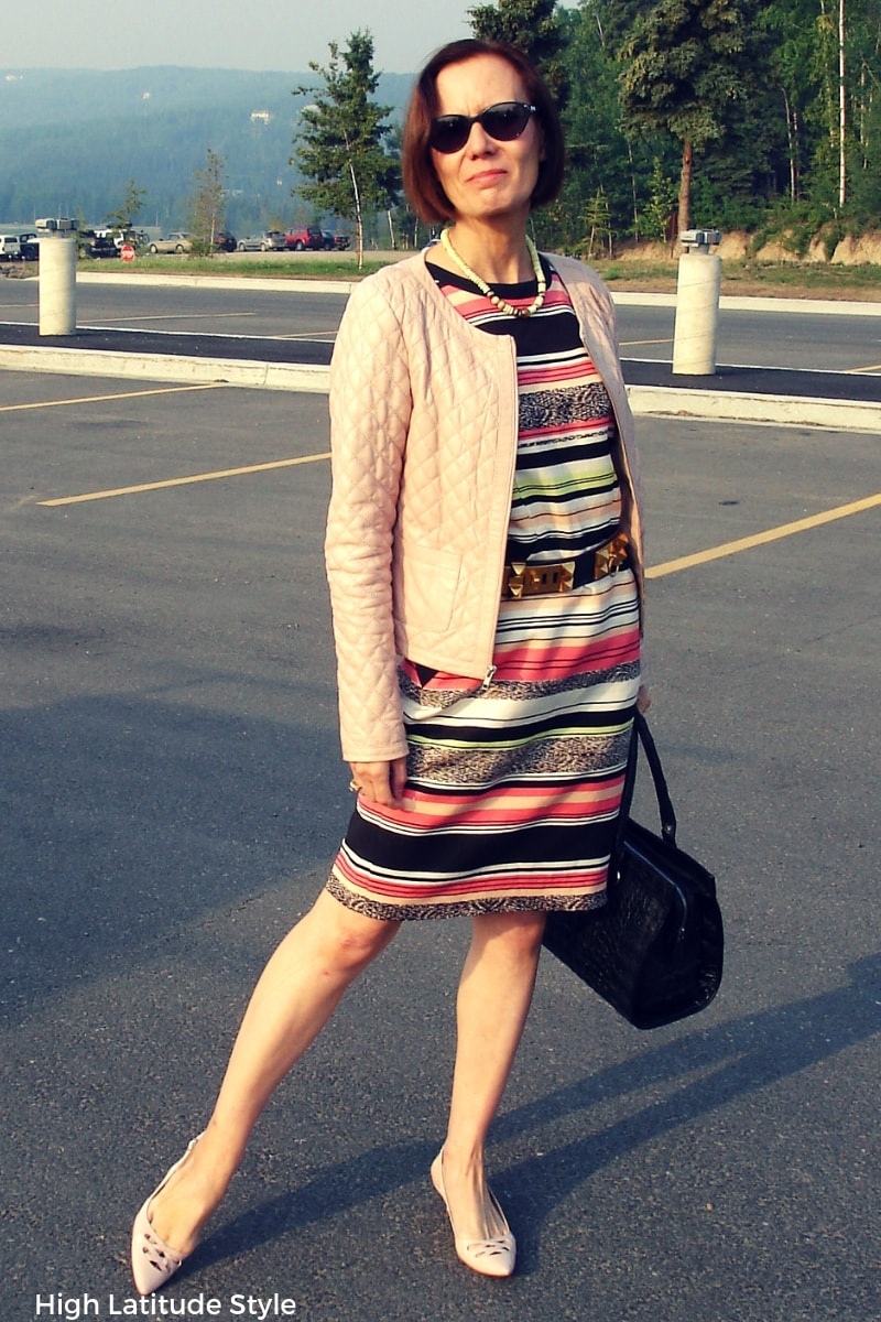 style blogger Nicole in summer to fall transition work outfit with striped sheath and quilted leather jacket
