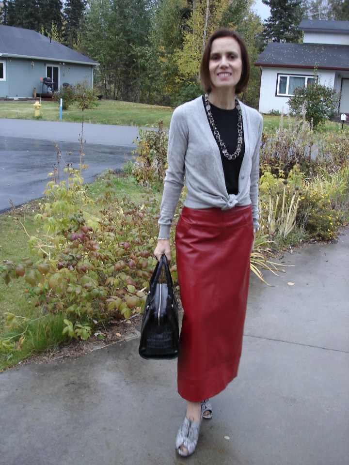 #agelessstyle midlife woman looking chic in a knit top and cardigan with long leather skirt