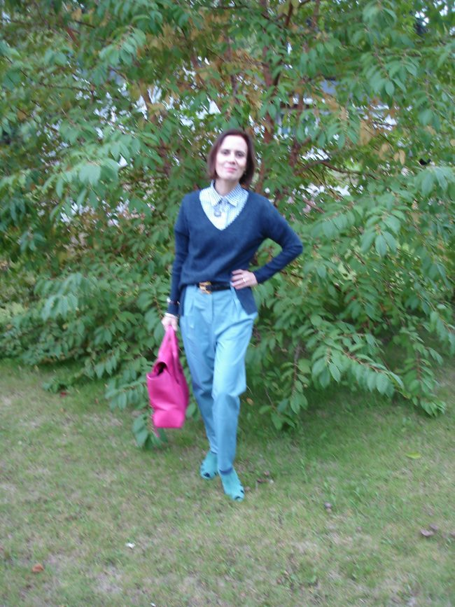 over 50 years old woman in leather pants, v-neck sweater, gingham button-down shirt and sandals