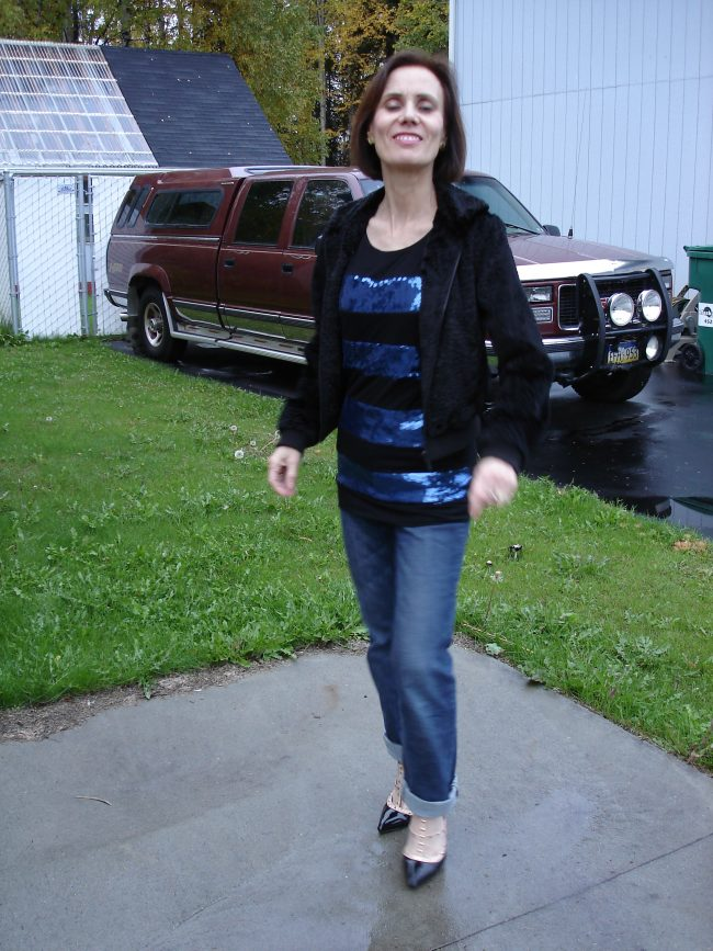 stylist in black with blue sequins striped tunic, BF jeans, faux fur bomber, studded pumps
