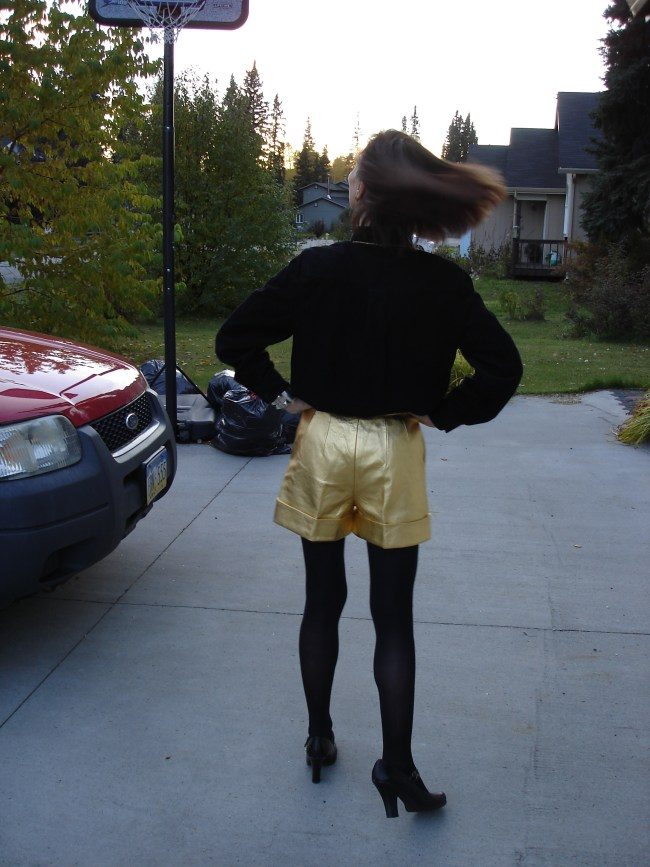 over 50 years old blogger in golden leather shorts with black top and tights