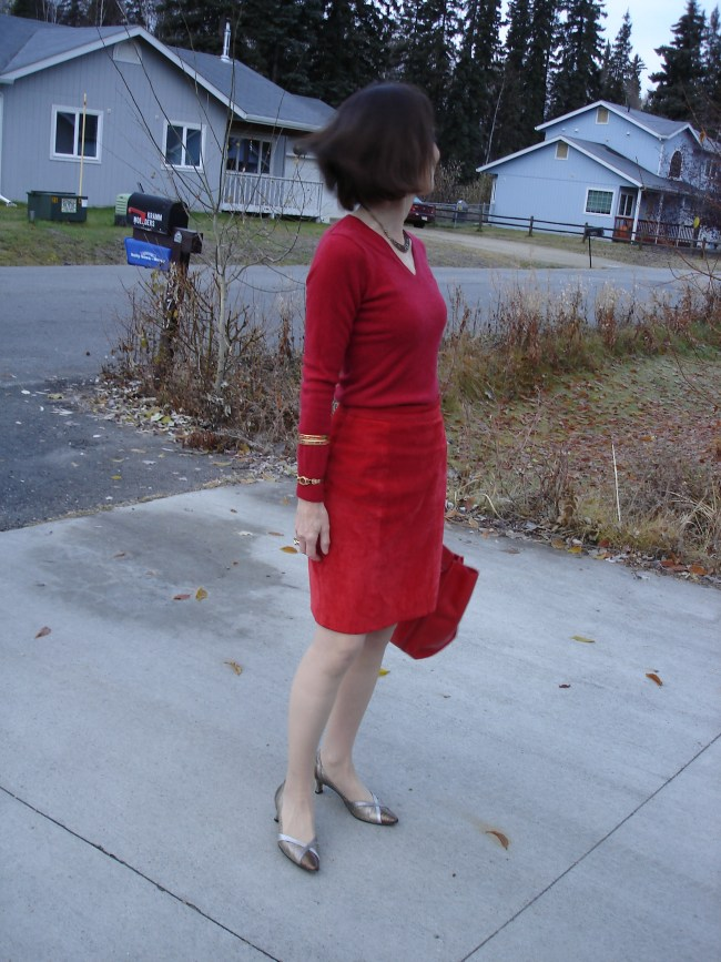 over 50 years old stylist in red suede skirt and sweater with matching bag