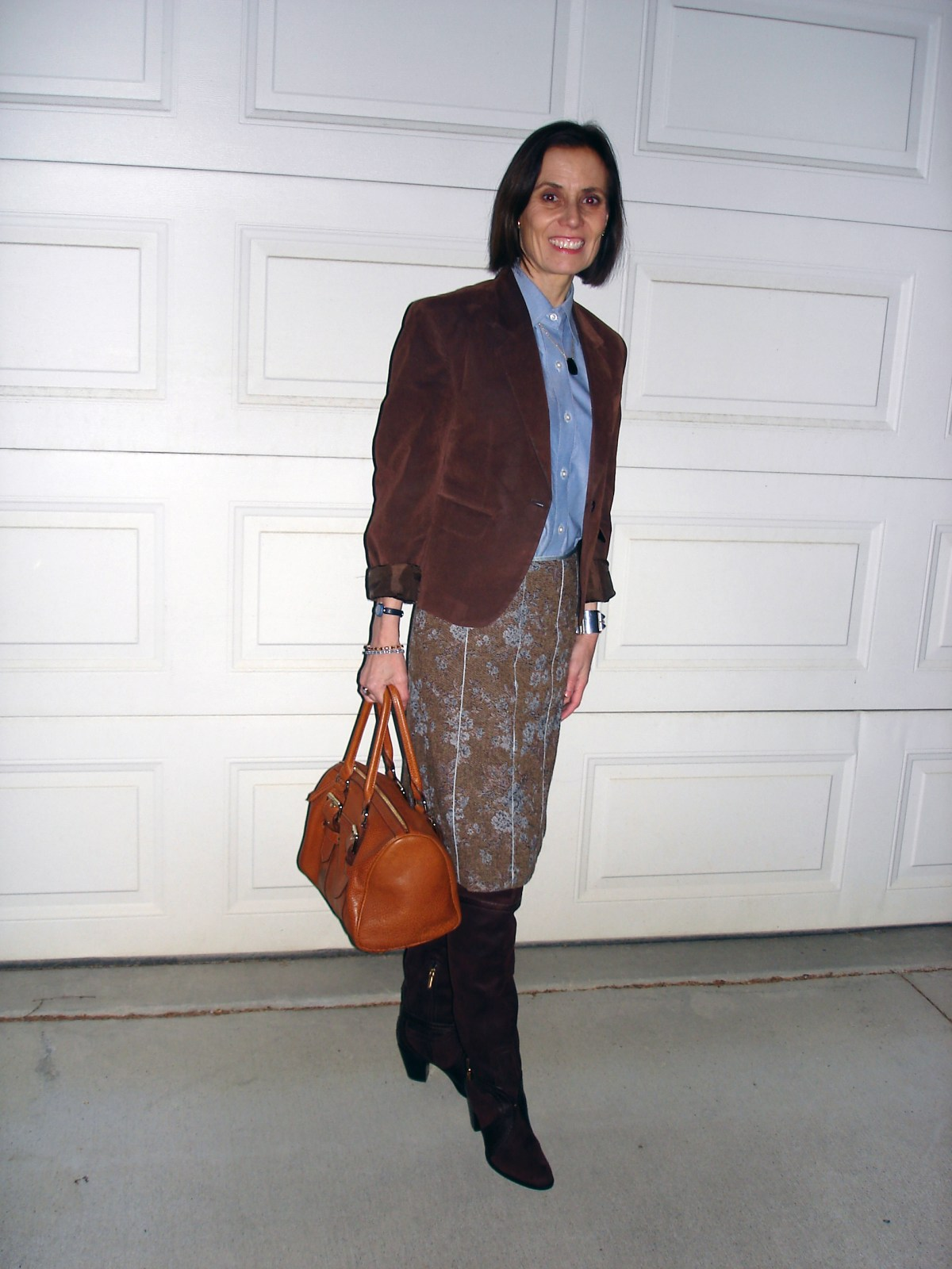 midlife woman in a tweed skirt with button-down shirt and suede blazer for a winter office look
