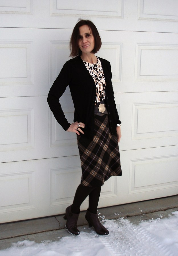 midlife style blogger in winter business casual outfit of plaid skirt, tights, ankle boots and accessories