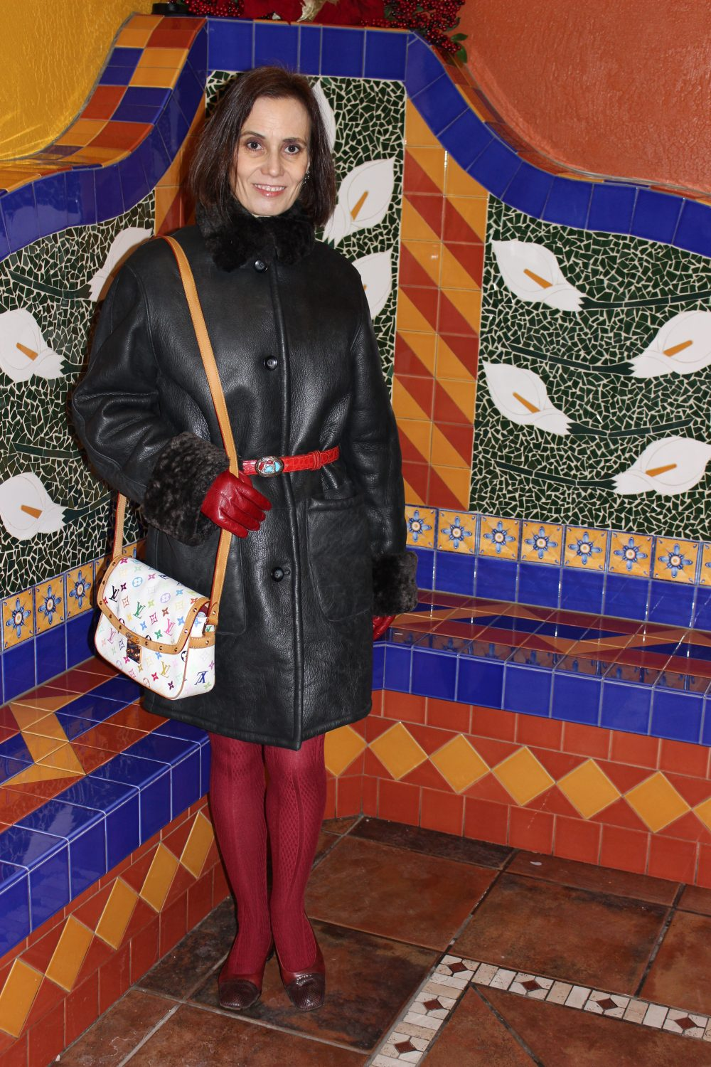 shearling coat with red belt, gloves, tight and shoes and a multi-color LV saddle bag