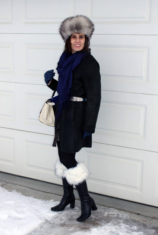 stylist in black boots with faux fur socks and shearling coat