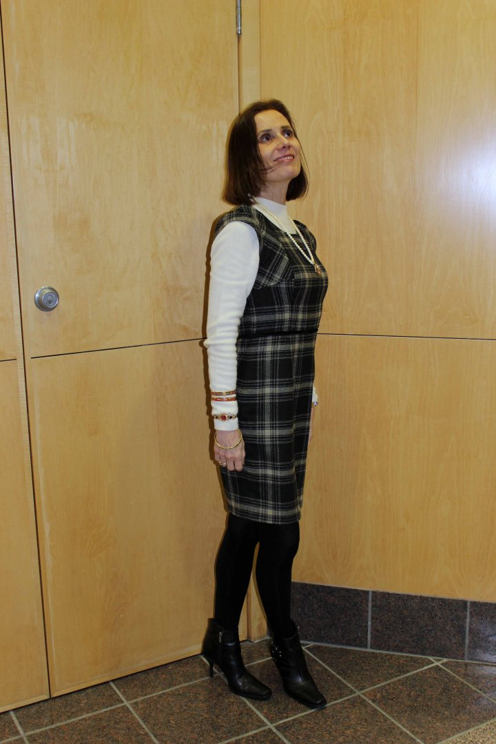 Nicole donning an office look with a plaid dress