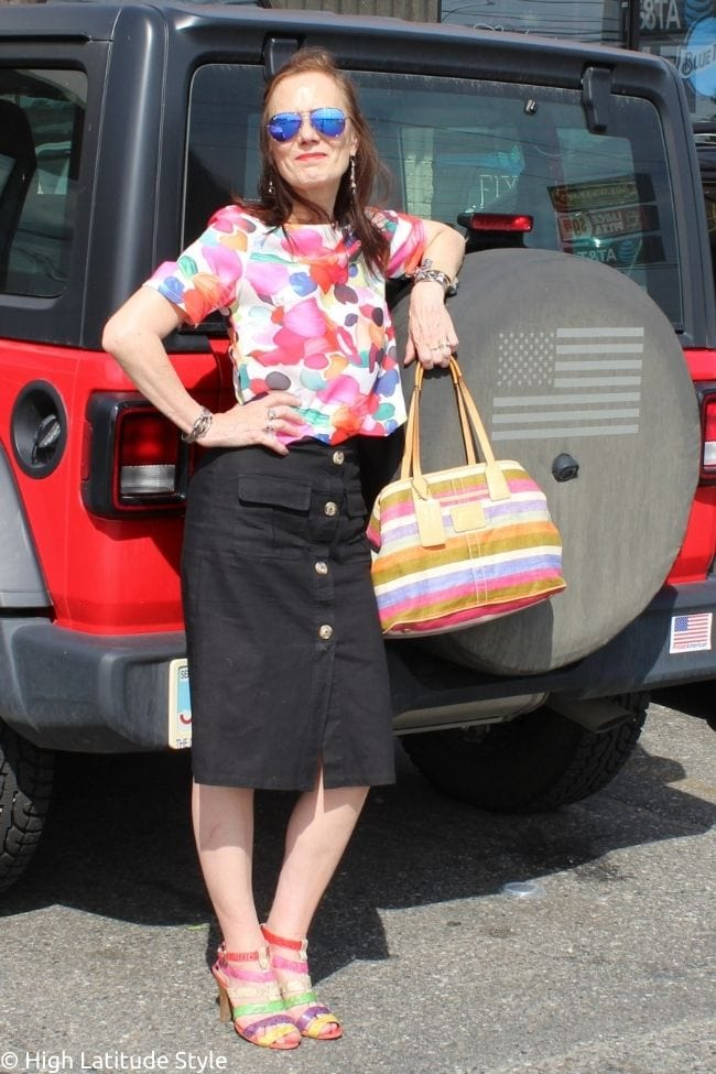 style blogger in button-down skirt,cropped floral top, mirrored sunnies, stripped bag