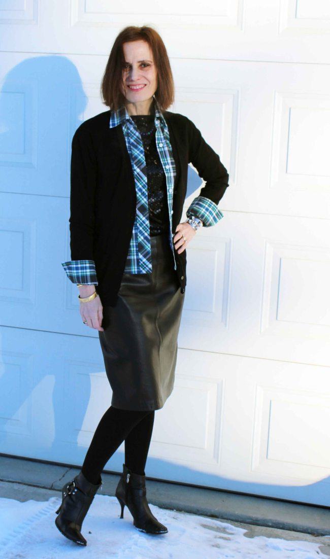 #fashionover50 mature woman in sequin top with plaid shirt in front of a background with light and shade