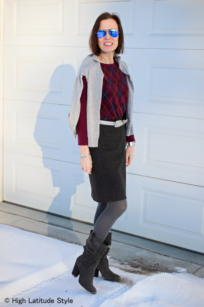 #fashionover50 woman in interesting winter look with tweet skirt with sweater and cardigan worn over the shoulders