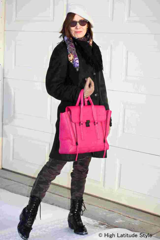 #fashionover50 midlife woman looking street chic in a shearling coat with fuchsia bag and camouflage cargo pants
