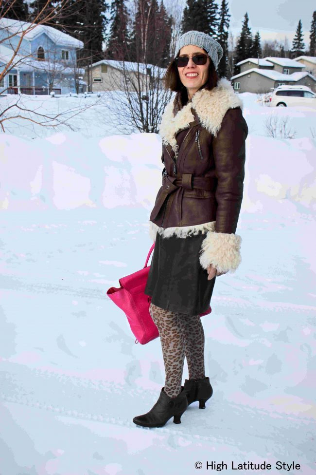 over 50 years old woman in shearling motorcyle jacket and pom pom hat with leo legwear