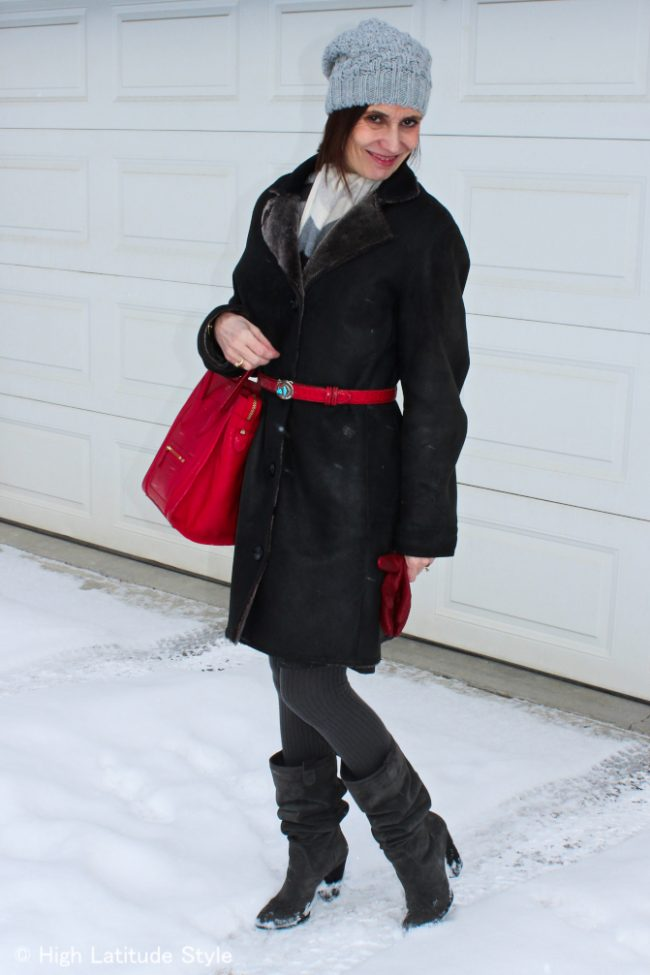 stylist with gray pom pom hat, red gloves and bag