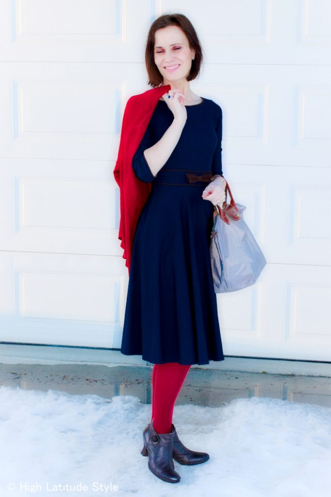 dancer in retro 1950s inspired blue dress with red cardigan and tights