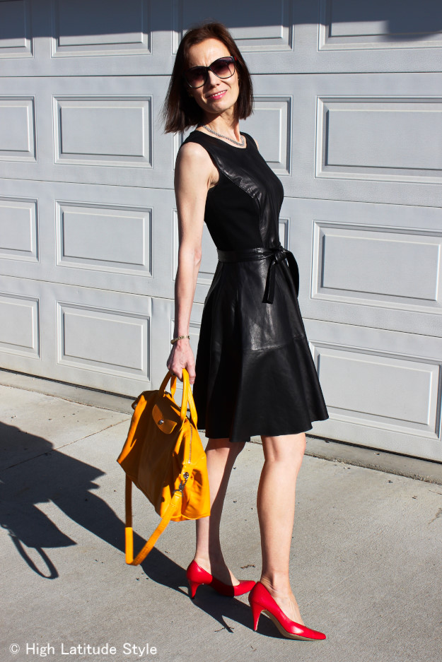 #fashionover40 midlife woman in chic Fit-and-flare-leather-dress with sunflower yellow bag and red pumps