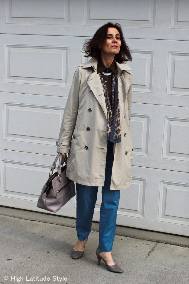 over 50 years old woman in blue leather trousers and classic British style trench coat