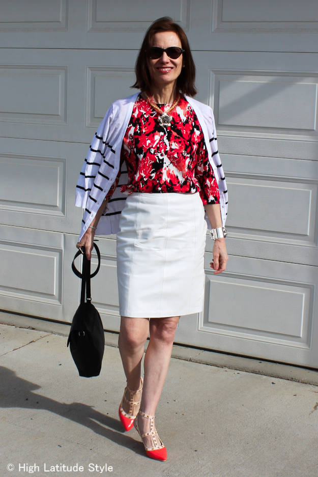 fashion blogger over 50 in leather skirt work outfit with two cardigans