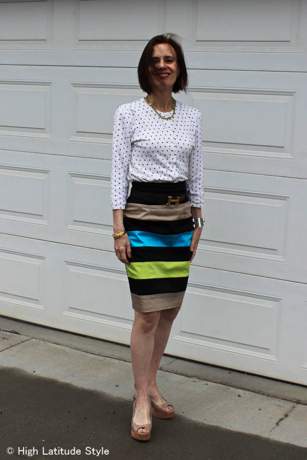 midlife woman in a work outfit with a polka dot top and a striped skirt