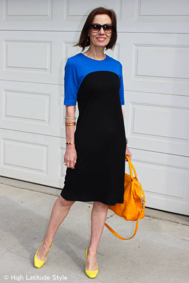 #fashionover50 woman in color block Ronen Chen dress with yellow bag and yellow shoes