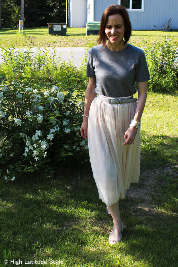 influencer in tulle skirt over 50 with cashmere sweater and belt reflecting the shades of pearls