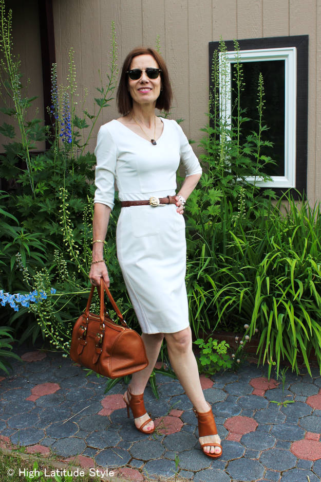 mature blogger in Victoria Beckham inspired V-neck dress styled for work with tan accessories, sandals and bag
