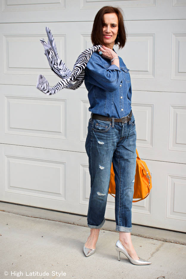 #styleover50 woman in distressed jean, denim shirt and zebra cardigan