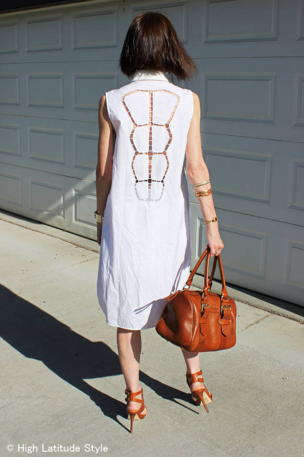#fashionover50 mature woman in a little white dress with large eyelet type lace in the back