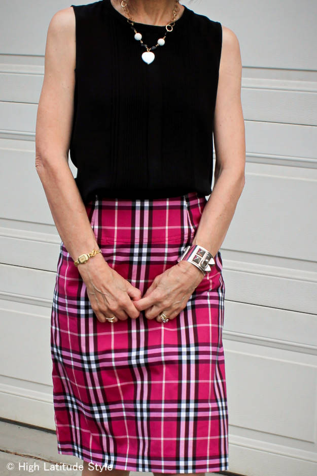 over 50 years old stylist in Burberry skirt with silk blouse and designer jade and onyx necklace
