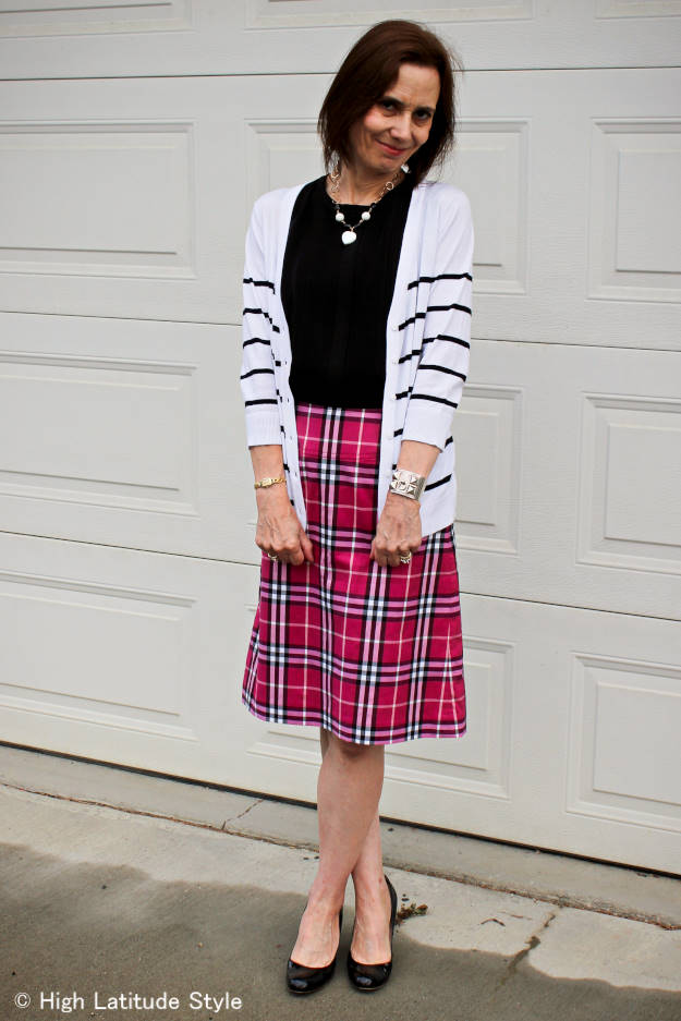 #AlmoJewellery #fashion-over-50 older woman looking psoh chic in a rose, black and white Burberry plaid bottom, black top and black and white necklace