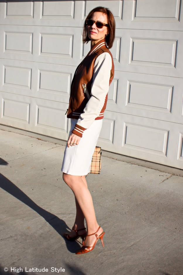 posh chic mature woman with sheath and baseball leather jacket