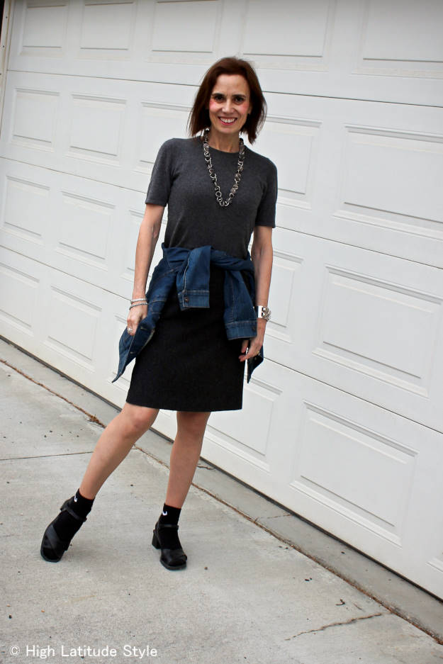style book author demonstrating how to wear the Normcore trend with socks, denim skirt and sweater
