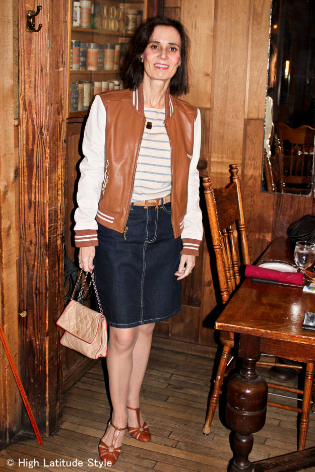 fashion blogger in posh casual outfit for the movies with denim skirt, baseball jacket, striped shirts