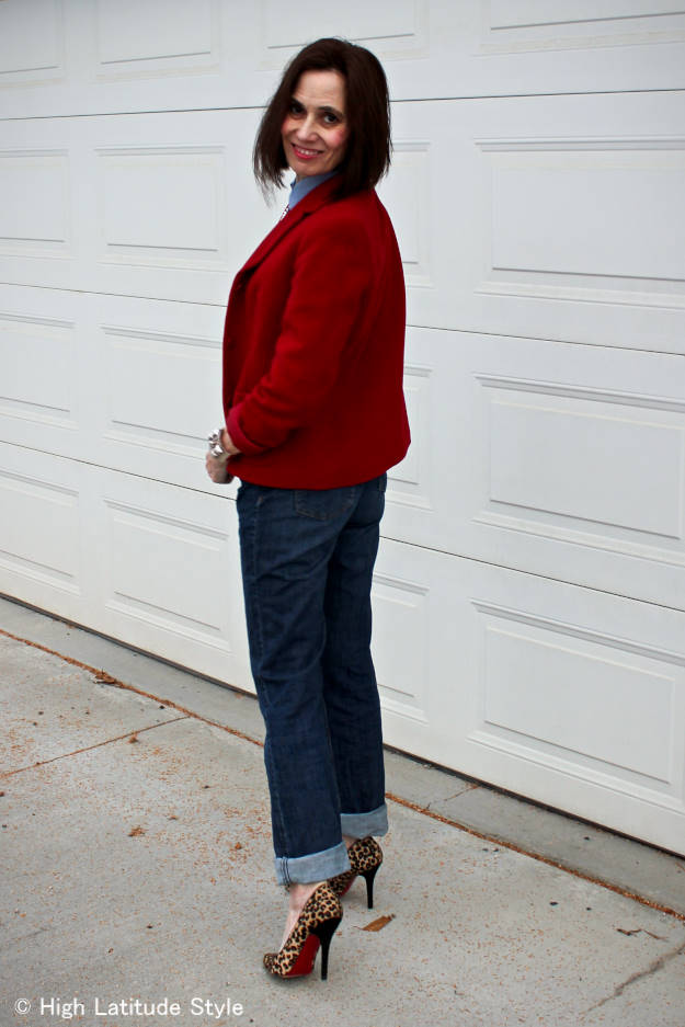 fashion blogger over 50 in blazer with jeans outfit with red blazer, chambrary shirt, pumps, and jeans