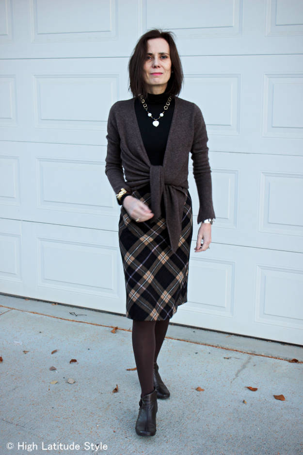 style blogger in winter office look with diagonal plaid skirt, turtleneck top, cardigan