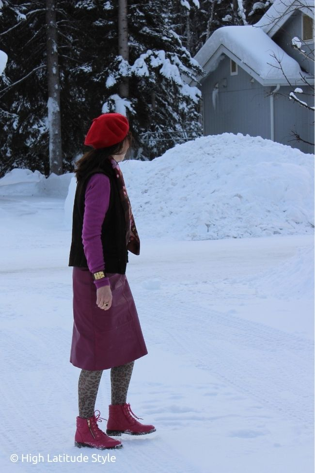 style book author in brown red pink outfit with vest, sweater leather skirt pattern tights and French hat
