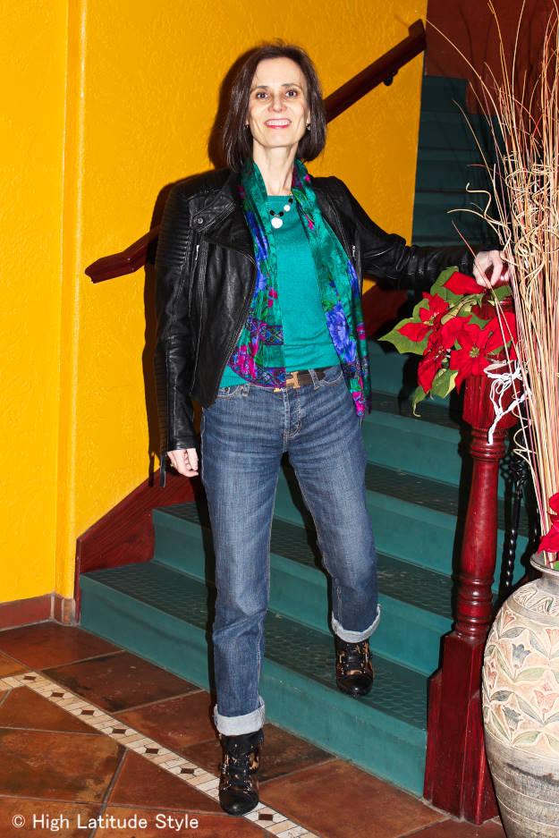 over 50 years woman wearing a biker jacket, sweater, wedge sneakers