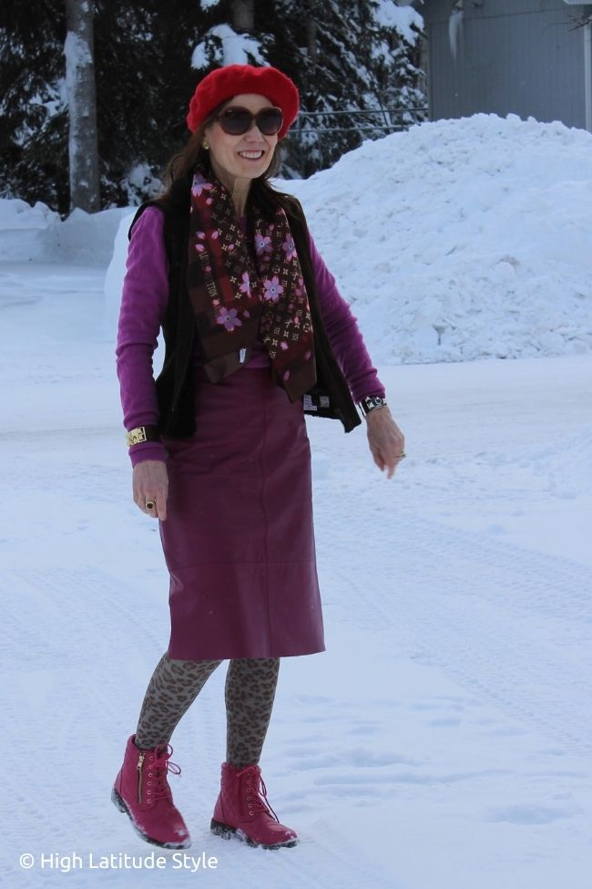 stylist in pink leather skirt, booties and sweater, brown vest and tights, printed scarf and red beret
