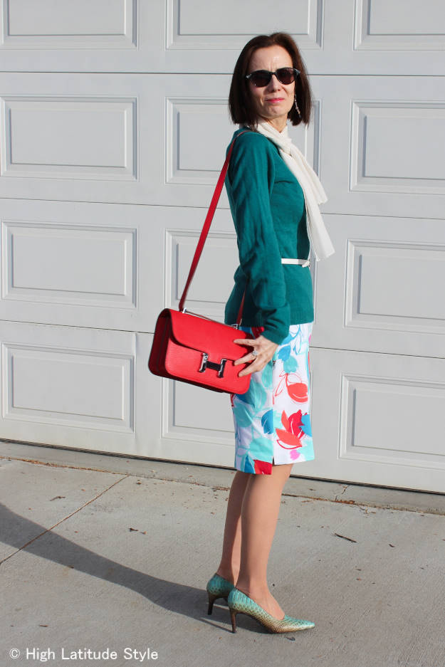 fashion blogger over 50 in abstract print summer dress worn as skirt with a sweater