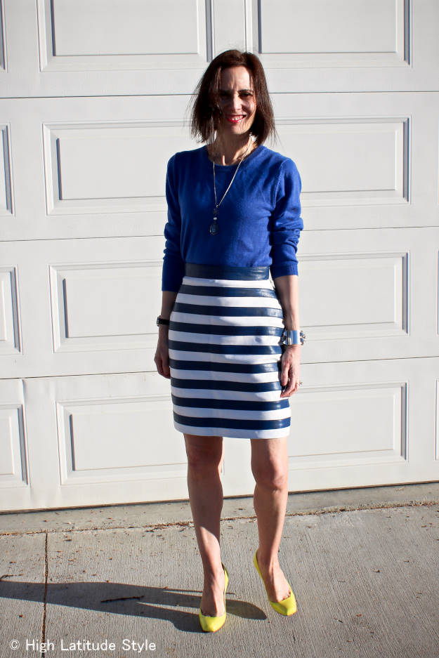 #over50fashion blogger in knee-length leather skirt, sweater, statement necklace and high neon color heels