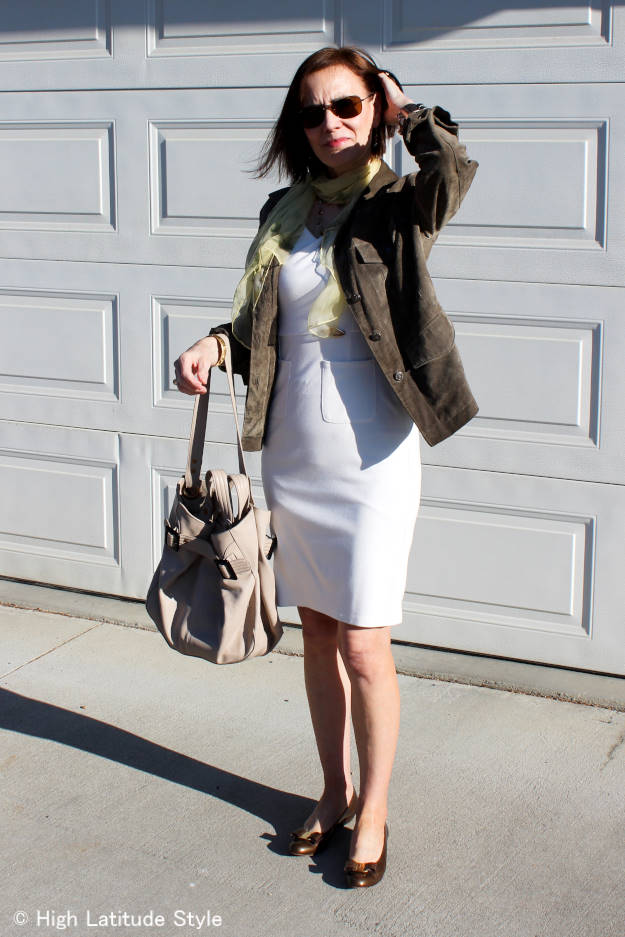 Fashion blogger in a sheath dress with suede utility jacket, flats, and tote