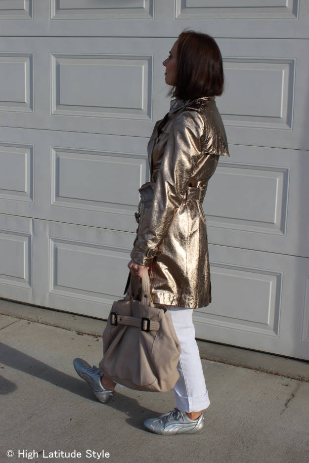 #styleover50 mature woman wearing a golden trench coat with silver sneakers