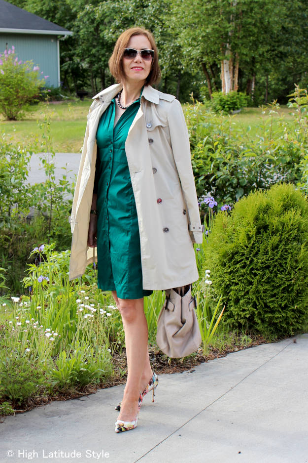 #fashionover50 style blogger in a Burberry Brit trench coat with thrifted shirt dress, floral pumps, and black pearl necklac