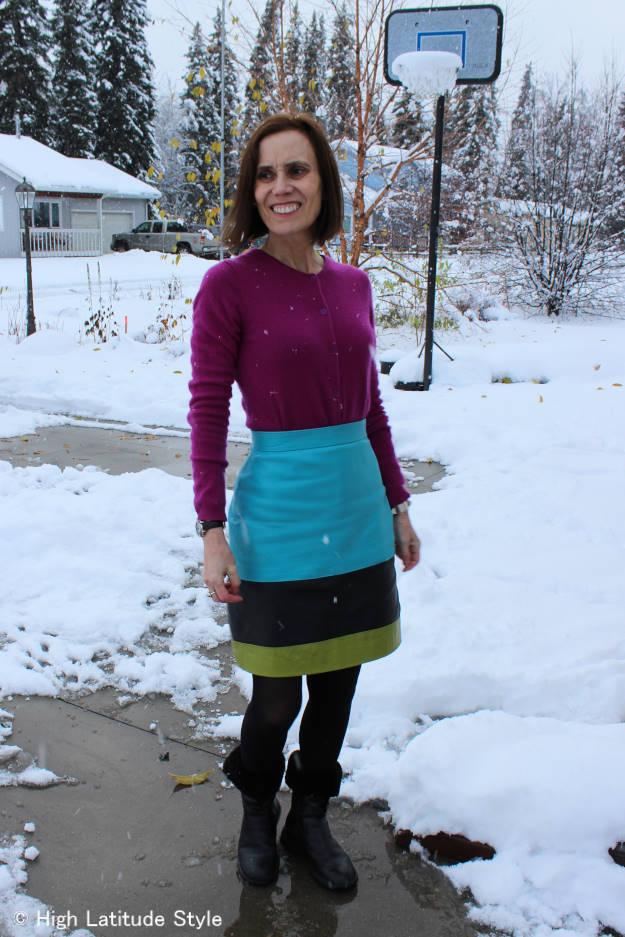 over 50 years old fashion blogger in color blocked outfit of black, turquoise, green and fuchsia